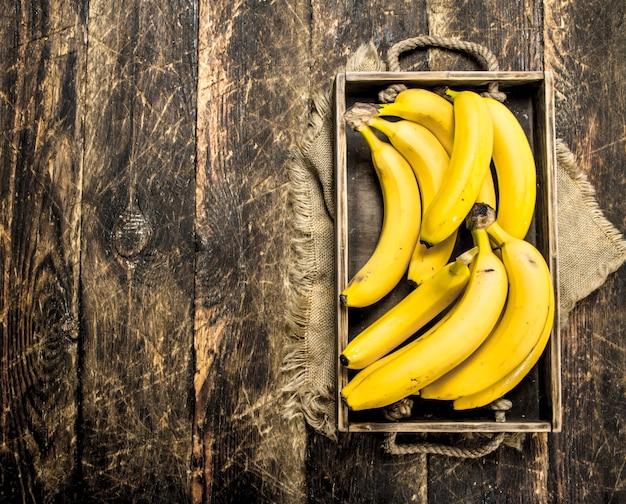 Świeże banany na starej tacy. na drewnianym tle.