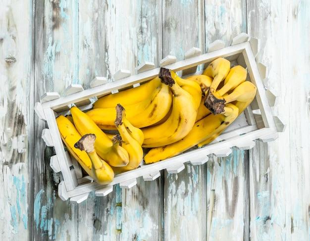 Świeże banany w białym plastikowym koszu.