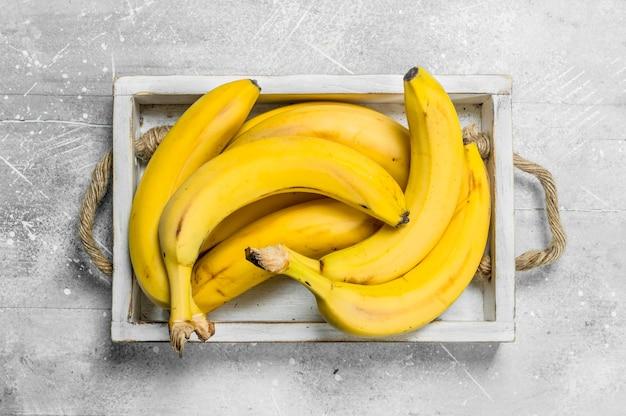 Świeże banany w drewnianym pudełku.