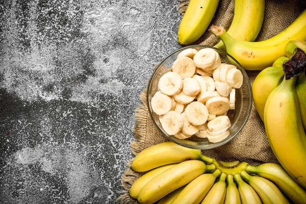 Świeże banany z kawałkami pokrojonych bananów w misce na rustykalnym stole.
