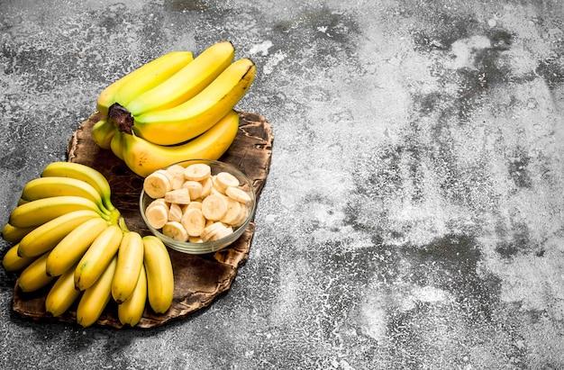 Świeże banany z kawałkami pokrojonych bananów w misce. na rustykalnym stole.