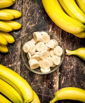 Świeże banany z posiekanymi kawałkami w misce. na drewnianym stole.