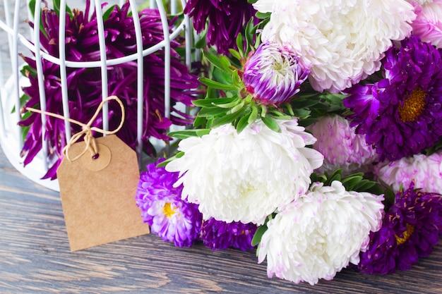 Świeże białe i fioletowe kwiaty aster na stole z pustą papierową etykietą