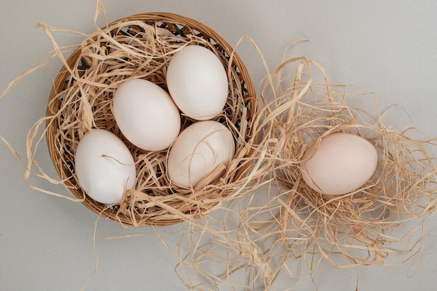 Świeże białe jaja kurze z siana na wiklinowym koszu.
