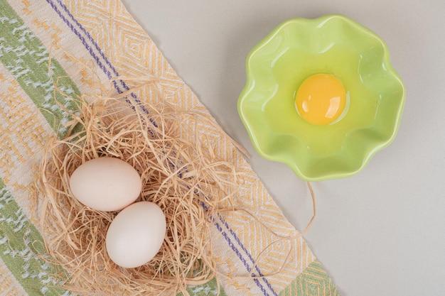 Świeże białe jaja kurze z żółtkiem na szklanej płytce.