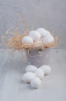 Świeże białe jajka w wiadrze na tle marmuru.