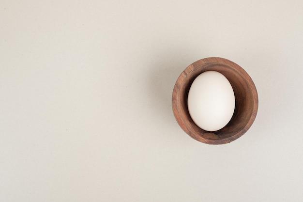 Świeże białe jajko z kurczaka w drewnianej misce.