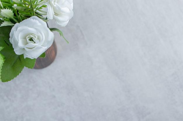Świeże białe kwiaty w drewnianym dzbanku, na białym stole.