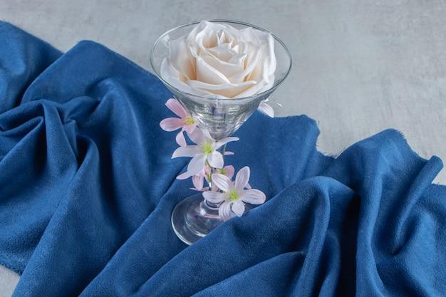 Świeże białe kwiaty w szklance na kawałku tkaniny, na białym stole.