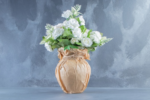 Świeże białe kwiaty w wazonie, na marmurowym tle.