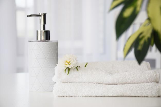 Świeże białe ręczniki złożone na białym stole, biały kwiat i pojemnik na płyn z zielonymi liśćmi rośliny domowej i tiulowym oknem na tle.