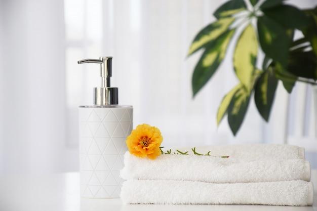 Świeże białe ręczniki złożone na białym stole, kwiat pomarańczy i pojemnik na płyn z zielonymi liśćmi rośliny domowej i tiulowym oknie na tle. koncepcja czyszczenia na sucho lub salon kosmetyczny.