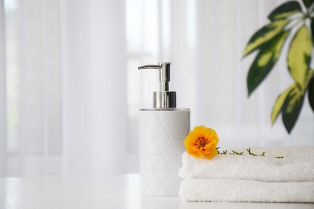 Świeże białe ręczniki złożone na białym stole, kwiat pomarańczy i pojemnik na płyn z zielonymi liśćmi rośliny domowej i tiulowym oknie na tle.