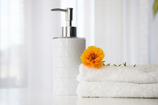 Świeże białe ręczniki złożone na białym stole z pomarańczowym kwiatem i pojemnikiem na płyn z tiulowym oknem na tle.