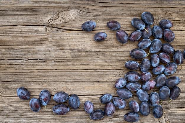Świeże błękitne śliwki na starym drewnianym stole