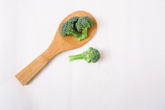 Świeże brokuły w drewnianej łyżce. białe tło. minimalistyczny styl. płaski układ. miejsce do kopiowania
