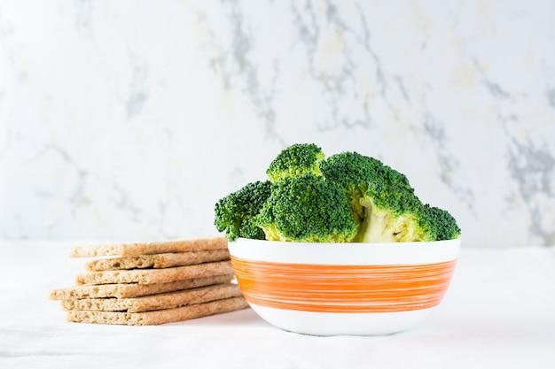 Świeże brokuły w misce i chrupiący chleb zbożowy na stole na szmatce. skopiuj miejsce