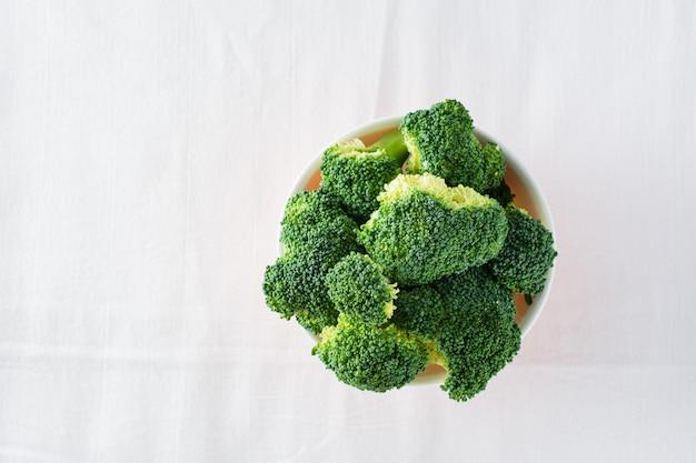Świeże brokuły w misce na stole na ściereczce. dieta zdrowa żywność. widok z góry. skopiuj miejsce