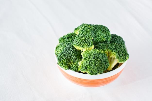 Świeże brokuły w misce na stole na ściereczce. dieta zdrowa żywność.