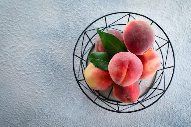 Świeże brzoskwinie. brzoskwinie w metalowym koszu
