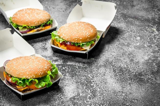 Świeże burgery w papierowych pudełkach. na rustykalnym stole.