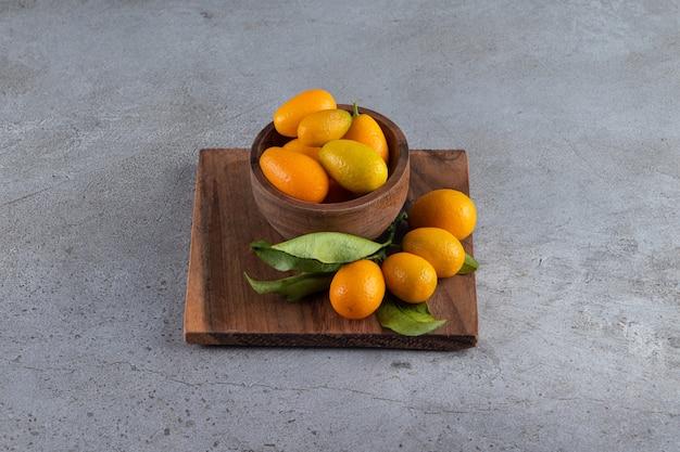 Świeże całe cytrusowe owoce cumquat z liśćmi.