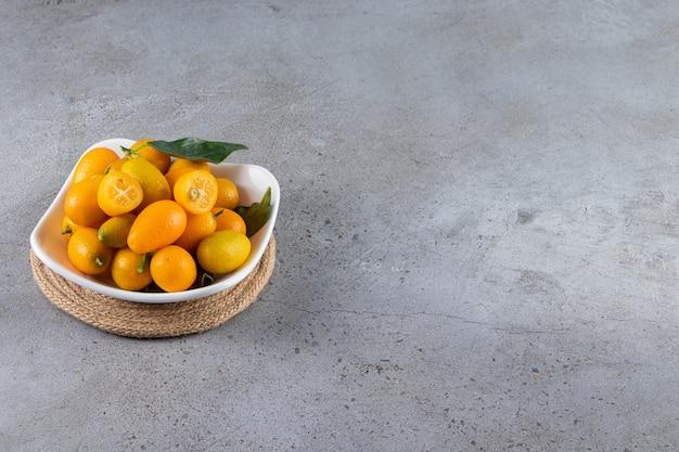 Świeże, całe i pokrojone owoce cytrusowe cumquat z liśćmi.