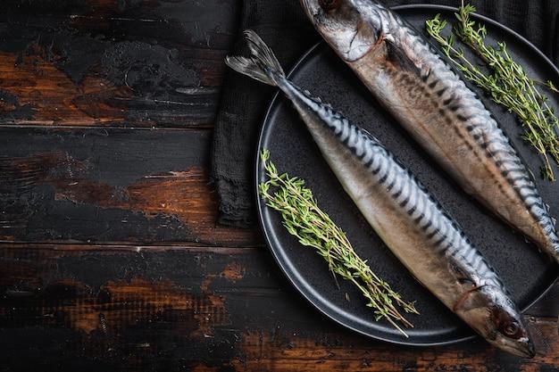 Świeże całe ryby morskie ze składnikami na drewnianym stole