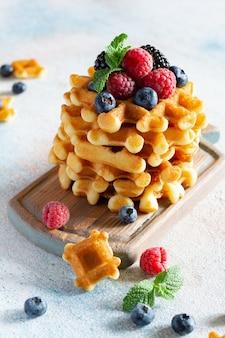 Świeże, chrupiące belgijskie gofry na śniadanie z dojrzałymi jagodami (maliny, borówki, jeżyny), miętą i cukrem pudrem na desce na jasnym tle.