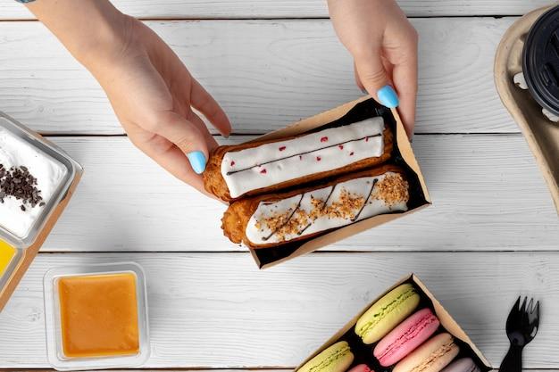Świeże ciasta eclair w tekturowym pudełku