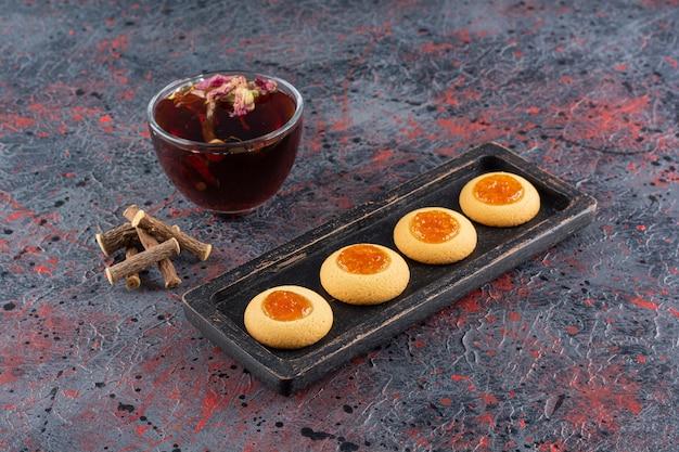 Świeże ciasteczka dżemowe z pachnącą herbatą w stylu rustykalnym.