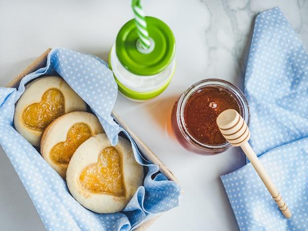 Świeże ciasteczka, szklanka mleka i słoik
