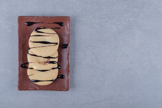 Świeże ciasteczka z sosem czekoladowym na brązowym talerzu