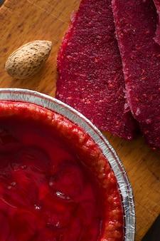 Świeże ciasto truskawkowe z orzechami na boku i mrożonymi jagodami ciasto truskawkowe na ciemnym stole