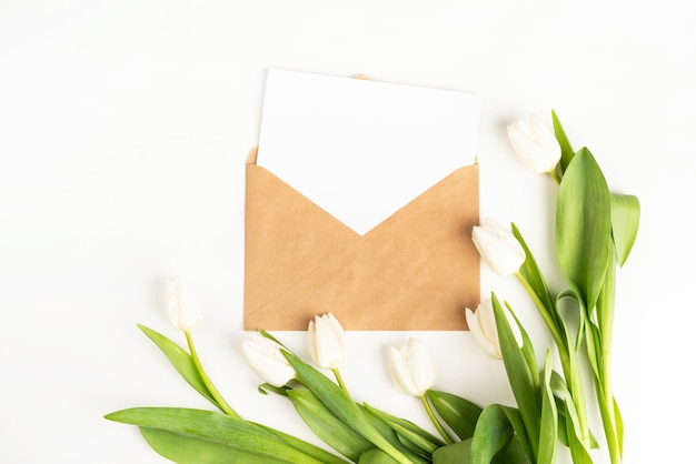 Świeże cięte białe tulipany kwiaty i pusta karta z widokiem z góry koperty na białym tle