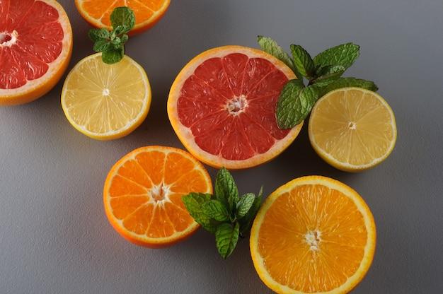 Świeże cytrusy i mięta przecięte na pół na szarym tle. soczyste grejpfruty, mandarynki, cytryny, pomarańcze, składniki soku cytrusowego, tło żywności