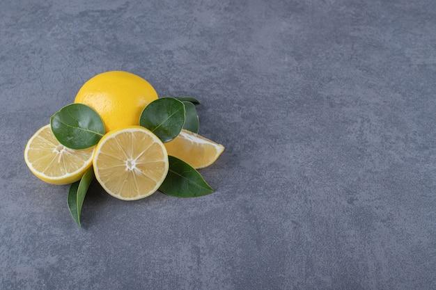Świeże cytryny w całości lub w połowie na szarym tle.