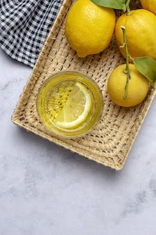 Świeże cytryny z zielonymi liśćmi mięty na marmurkowym stole z góry. leżał na płasko