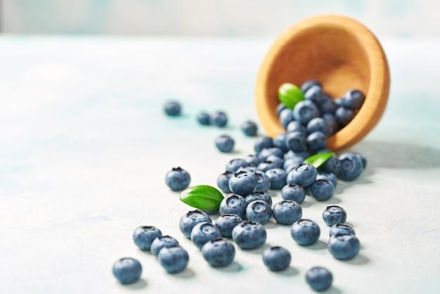 Świeże czarne jagody rozpraszają od drewnianego pucharu na turkusowym tle, selekcyjna ostrość.