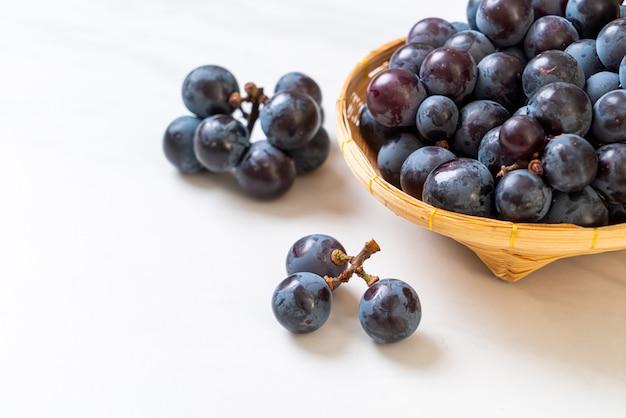 Świeże czarne winogrona na białym tle