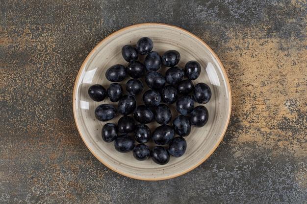 Świeże czarne winogrona na talerzu ceramicznym.