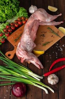Świeże czerwone całe mięso królika na drewnianej desce do krojenia, widok z boku