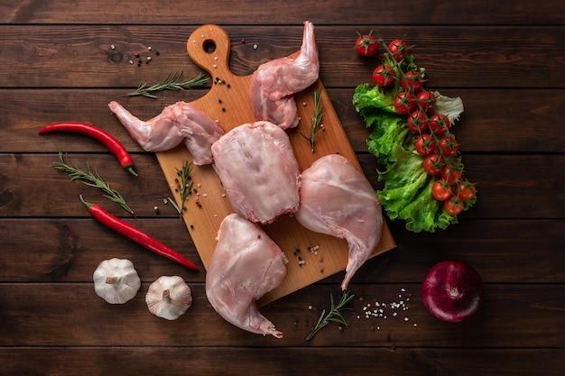 Świeże czerwone całe mięso królika ze świeżymi warzywami na drewnianej desce do krojenia, widok z góry