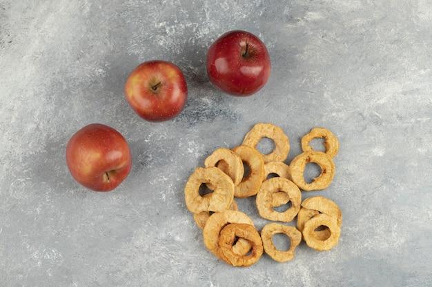 Świeże czerwone jabłka i suszone krążki na marmurze.