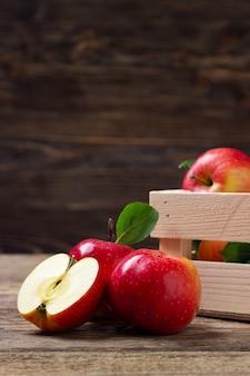 Świeże czerwone jabłka na drewnianym