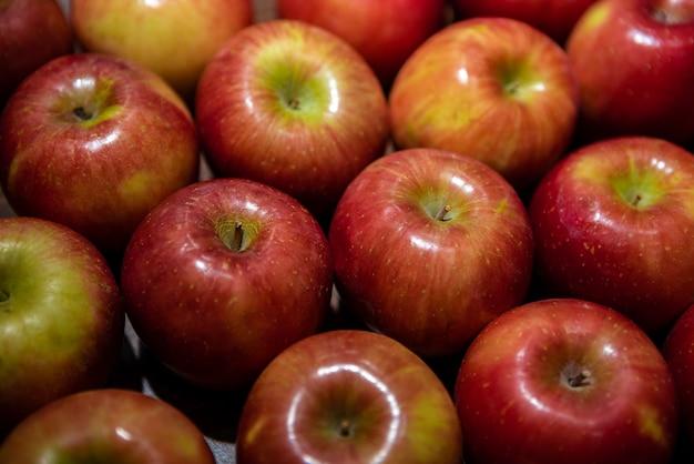 Świeże czerwone jabłka na ladzie rynku. jabłka w kartonowym pudełku na półce w sklepie spożywczym. zamknij widok owoców w supermarkecie. zdrowe odżywianie i wegetarianizm