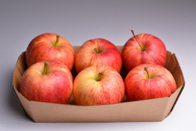 Świeże czerwone jabłka na tacce z papieru celulozowego
