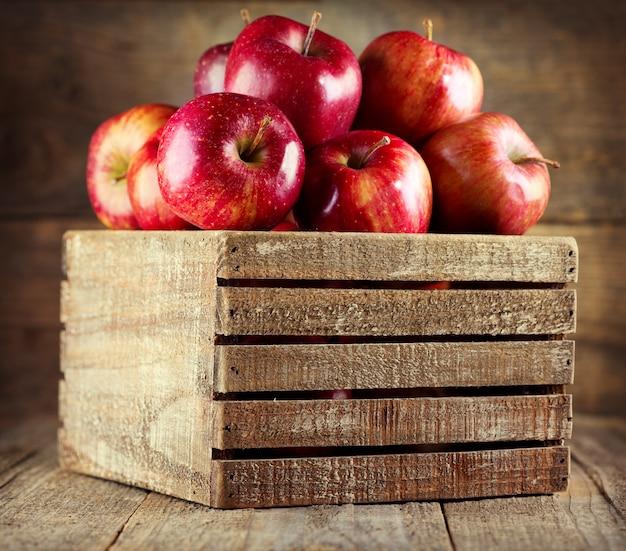 Świeże czerwone jabłka w drewnianym pudełku