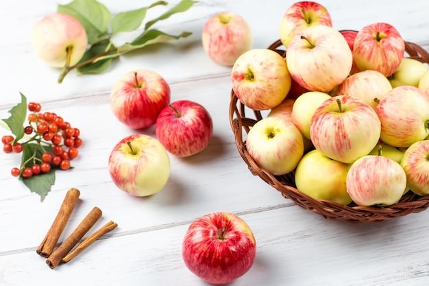 Świeże czerwone jabłka w wiklinowym koszu i cynamonie