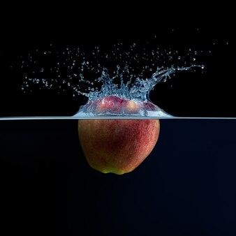 Świeże czerwone jabłko wpadające do wody na czarnej odizolowanej powierzchni. zbliżenie.